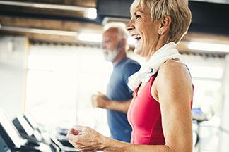 elderly couple walking on treadmills